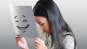 An image showing a girl masking her face with a piece of paper that has a smiling face drawn on it